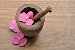 Flowers in a pestle for aromatherapy and spa. On a wooden background Royalty Free Stock Photo