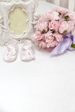 Flowers, photoframe and children's sandals on the bed. A gift for the newborn and mother. Pink flowers, photoframe and children's sandals on the bed Royalty Free Stock Photo