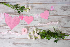 Flowers, pink ribbons, paper valentines. Bunch of flowers, pink ribbons, paper valentines lie on a light wooden background Stock Images
