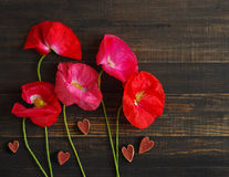 Flowers of pink wild poppy and red wooden hearts. Poppy bouquet of flowers on an old wooden background. Stock Photo