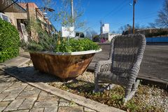 Flowers planted in a vintage bathtub. January 7, 2016 Comfort, Texas, USA: flowers planted in a vintage bath tub on the street in the small historic town Stock Photos