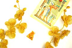Flowers and plants of gold color, a pattern on papyrus and ornaments in a pouch Stock Photos