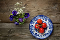 Flowers and plate with fresh tomatos Stock Photography
