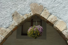 Flowers in pot hanging under stone arch Stock Images