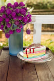 Flowers and rainbow cake on terrace Stock Photography