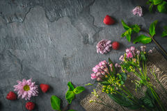 Flowers  , raspberries and mint on the dark stone background Royalty Free Stock Images