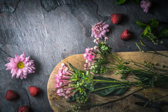 Flowers  , raspberries and mint on the dark stone table top view. Horizontal Royalty Free Stock Images