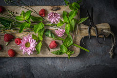 Flowers  , raspberries and mint on the wooden board. Top view horizontal Royalty Free Stock Photography