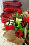 Flowers and red baskets. Bouquets of red, green and white flowers placed against stacked red plastic supermarket shopping baskets Stock Photography