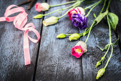Flowers with ribbon on old blue wooden table Stock Photos