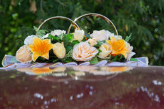 Flowers and rings on roof of wedding car Stock Images
