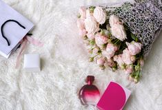 Flowers roses in a beautiful bouquet, a box with a holiday gift. And a bottle of perfume on a light background, close-up royalty free stock image