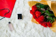 Flowers roses in a beautiful bouquet, a box with a holiday gift. And a bottle of perfume on a light background, close-up royalty free stock photo