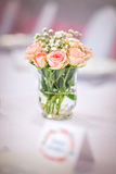 Flowers of roses on wedding table with card, romantic pink background for party or event Royalty Free Stock Photography
