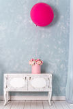 Flowers in round luxury present box and big pink balloon on chest of drawers. Bouquet of pink and white peonies in paper Royalty Free Stock Image