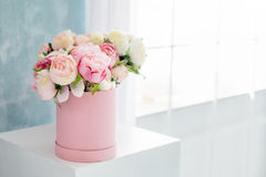 Flowers in round luxury present box. Bouquet of pink and white peonies in paper box near the window.Mock-up of hat box Royalty Free Stock Photo