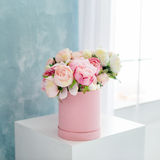 Flowers in round luxury present box. Bouquet of pink and white peonies in paper box. Mock-up of hat box of flowers Stock Image