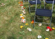 Flowers scatted on a wedding aisle in a lawn. Artificial flowers are scatted and planted on a wedding aisle stock image