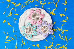 Flowers shaped cookies decorated with ornaments on blue backgrou Royalty Free Stock Images