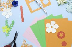 Flowers and shapes cut from colored paper. Scattered on a blue background royalty free stock photography