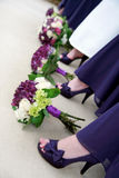 Flowers and Shoes of Bride and Bridesmaids. A happy bride stands with her bridesmaids showing off their flowers and shoes royalty free stock photo