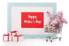 Flowers on shopping trolley and gifts. Shopping trolley with brenches of Lilac, gift boxes and frame with blank space on white background. Copy space for adding Stock Photo