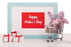 Flowers on shopping trolley and gifts. Shopping trolley with brenches of Lilac, pearl beads, gift boxes and frame with blank space on white background. Copy Stock Photos