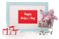 Flowers on shopping trolley and gifts. Shopping trolley with brenches of Lilac, pearl beads, gift boxes and frame with blank space on white background. Copy Royalty Free Stock Photo