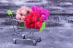 Flowers in a shopping trolley. Red, peach, lilac artificial flowers. Artificial flowers as a gift Royalty Free Stock Image