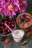 Flowers and Smoothie with fresh berries. Smoothie with fresh berries, nuts, seeds, fruit.  Healthy breakfast and almond milk Royalty Free Stock Photos