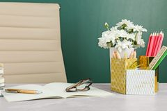 Flowers and stationery on table near chalkboard. Happy teacher`s day