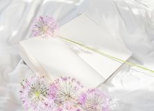 Flowers staying on open book in bed. Romantic good morning. Top view royalty free stock photography
