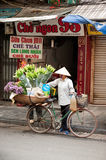 Flowers street vendor at Hanoi city,Vietnam. HANOI,VIETNAM-OCTOBER 12 : Daily life of the flower vendors sell on her bicycle in the typical street near old town Royalty Free Stock Images