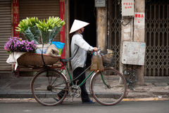 Flowers street vendor at Hanoi city,Vietnam. HANOI,VIETNAM-OCTOBER 12 : Daily life of the flower vendors sell on her bicycle in the typical street near old town Stock Images