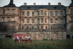 Flowers in suitcase against backdrop of ancient castle. Surrealism and mysticism Royalty Free Stock Photo