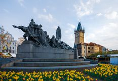 Prague Astronomical Clock behind the Jan Hus Monument surrounded by Daffodils in the middle of Spring stock photos