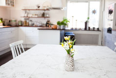 Flowers at the table in the foreground kitchen blurred in the background. Flowers at the kitchen table in the foreground and a fancy kitchen interior unfocused royalty free stock images