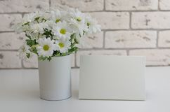 Flowers on the table with a greeting card close-up.White chrysanthemums in a vase on a stone background royalty free stock photos