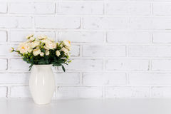 Flowers on the table over white brick wall. Background royalty free stock images