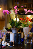 Flowers on the table in a restaurant. Orchid flowers in a decorative vase on a wooden table with candles and cutlery stock images