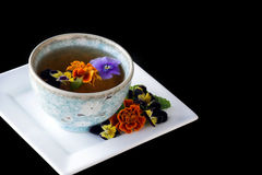 Flowers in Tea Cup. On white saucer with black background stock images