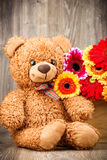 Flowers and a teddy bear. On wooden background Royalty Free Stock Photos