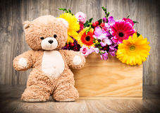 Flowers and a teddy bear. On wooden background Royalty Free Stock Image