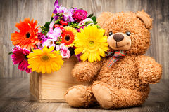 Flowers and a teddy bear. On wooden background Stock Photography
