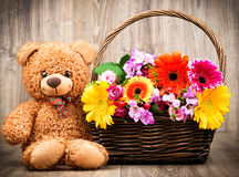 Flowers and a teddy bear. On wooden background Stock Images