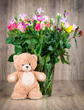 Flowers and a teddy bear. On wooden background Stock Photo