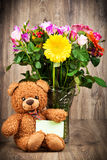 Flowers and a teddy bear. On wooden background Stock Photos
