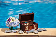 Flowers textile stuffed fish and treasure chest next to the pool Royalty Free Stock Photo