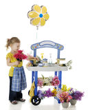 Flowers Tickle My Nose. An adorable preschooler scrunching her nose behind the flowers she holds by her flower stand.  Signs on the stand left blank for your Royalty Free Stock Photos