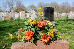 Flowers on a tombstone in a cemetary. With hundreds of tombstones in the background Stock Photography